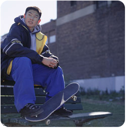 A student rests on a bench after skateboarding.